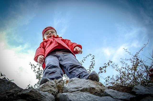 chłopczyk na występie skalnym spogląda z góry