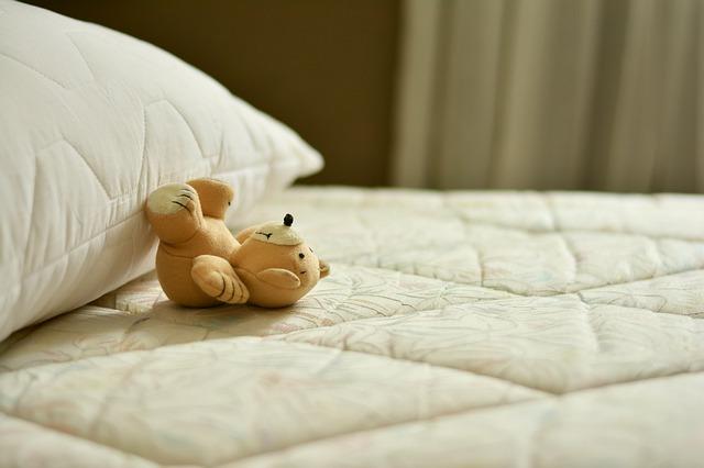 pościelone łóżko i pluszak